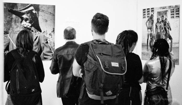 Audience looking at pictures of Leah Gordon's show KANAVAL in 2014.