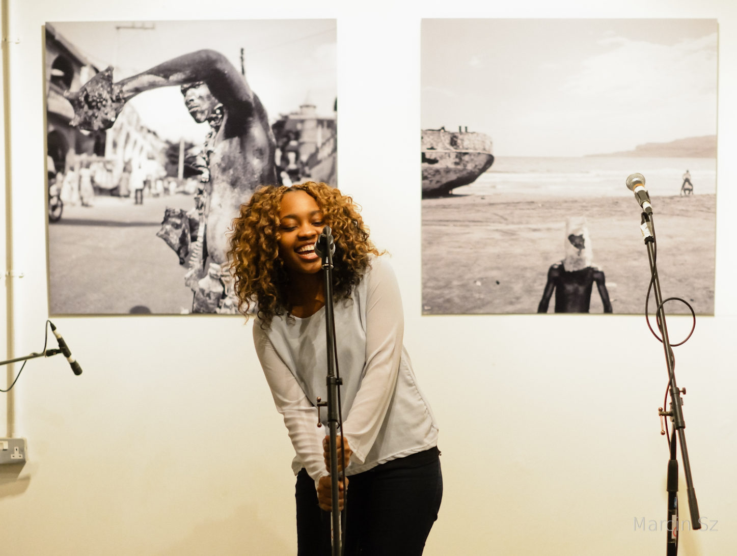 An image of a young woman performing in front of a photographic exhibition using a microphone and laughing. Picture by Marcin Sz.