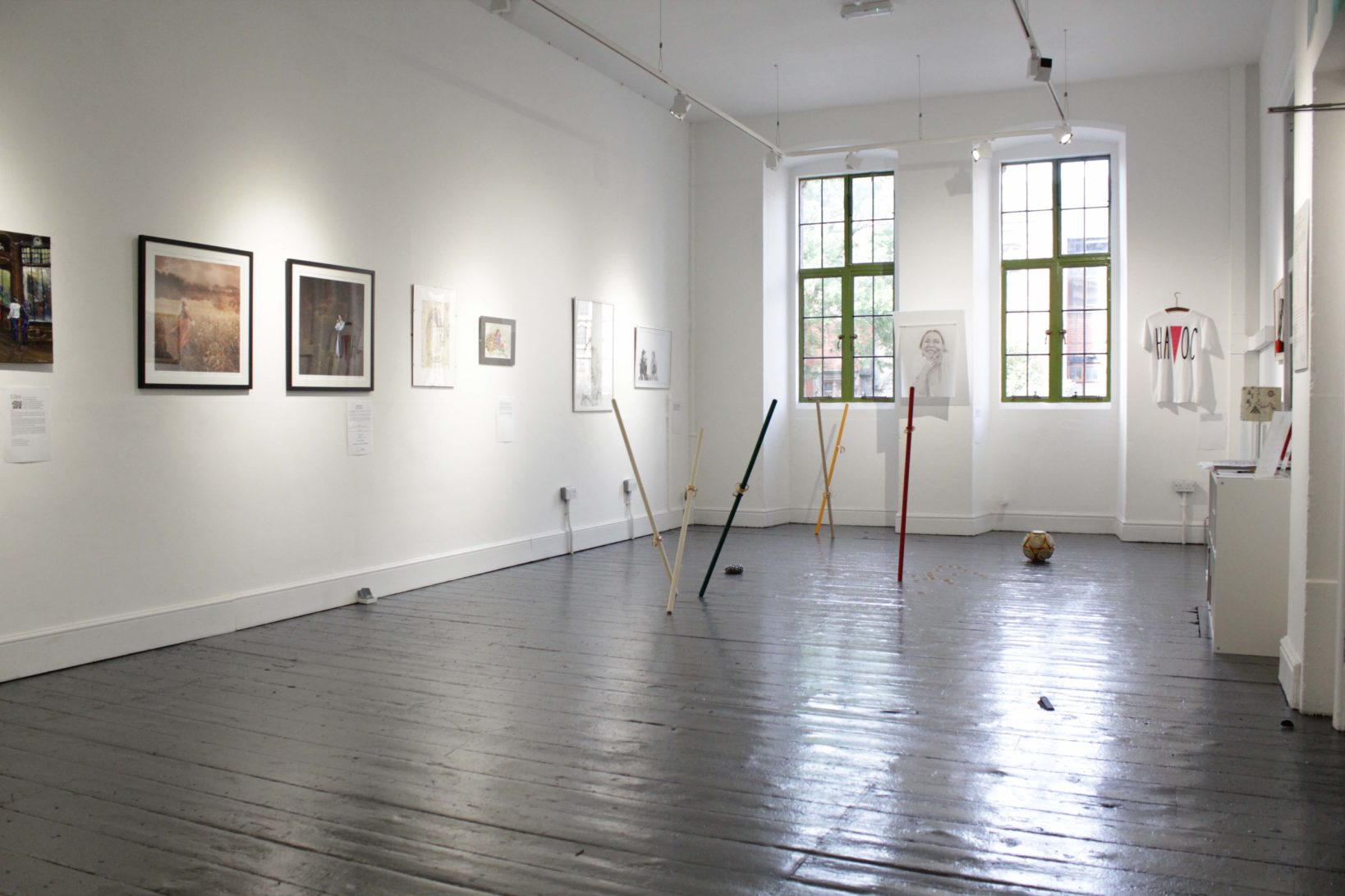An image of the members show 2019 on show at Ort Gallery in August and September 2019. You can make you several art works on the walls such as photographs, drawings and prints. There is also a floor based installation by Hira Butt where wooden sticks are sticking out of the floor and bangles are lying on the floor.