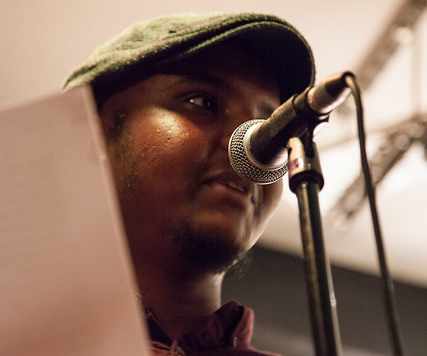 An image of artist and poet Ahmed Magare performing a poem using a microphone.